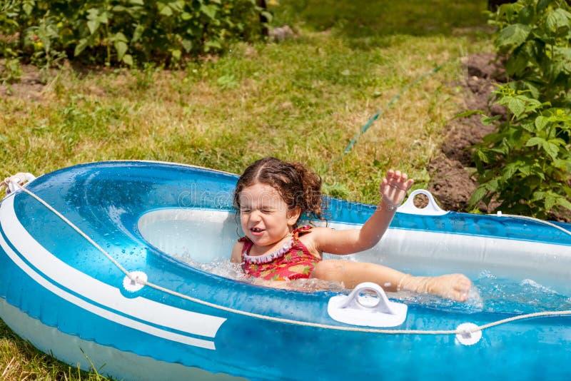 Mädchen, das im aufblasbaren Boot mit Wasser spielt lizenzfreie stockfotografie