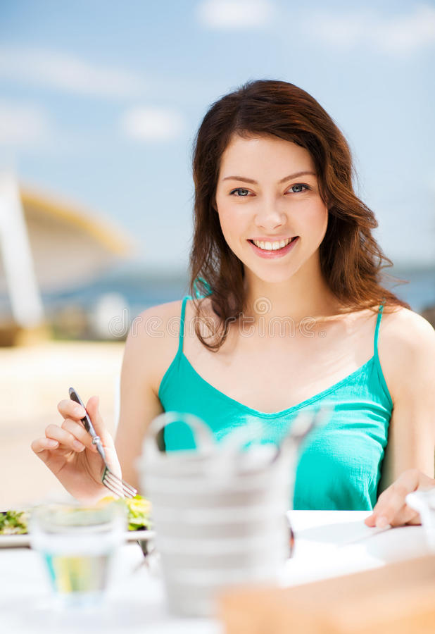 Mädchen, das im Café auf dem Strand isst stockbild