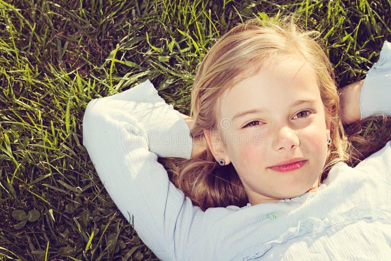 Mädchen, das im Gras liegt stockbild