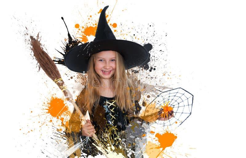 Mädchen, das im Hexenkleid mit Besen und Spinne, kleine Hexe Halloweens aufwirft stockbild