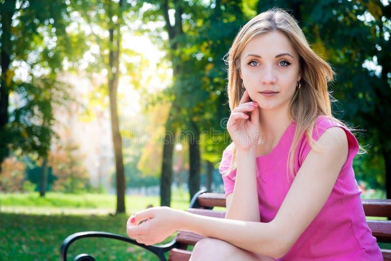 Mädchen, das im Park sitzt lizenzfreie stockfotos