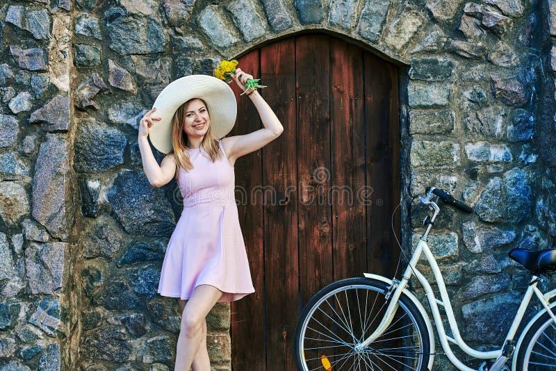 Mädchen, das im rosa Kleid, Strohhut aufwirft das Porträt, stehend nahe strukturiertem Stein, alter Wand und Holztür lächelt lizenzfreie stockfotos