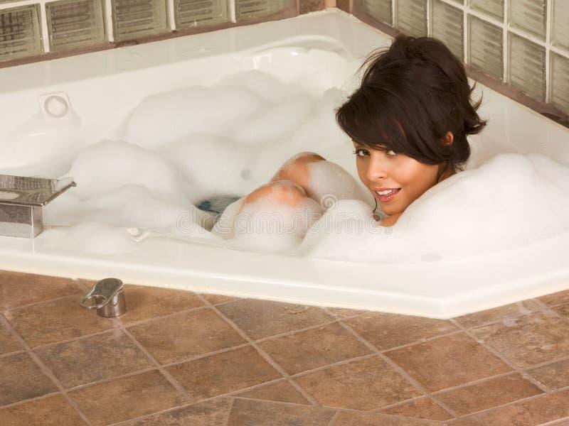 Mädchen, das im Schaumgummibad sich entspannt lizenzfreie stockbilder