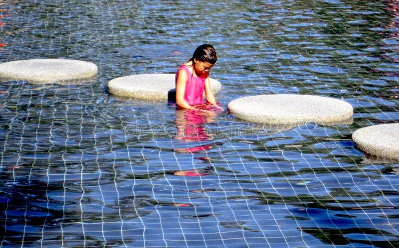 Mädchen, das im Wasser watet stockfoto