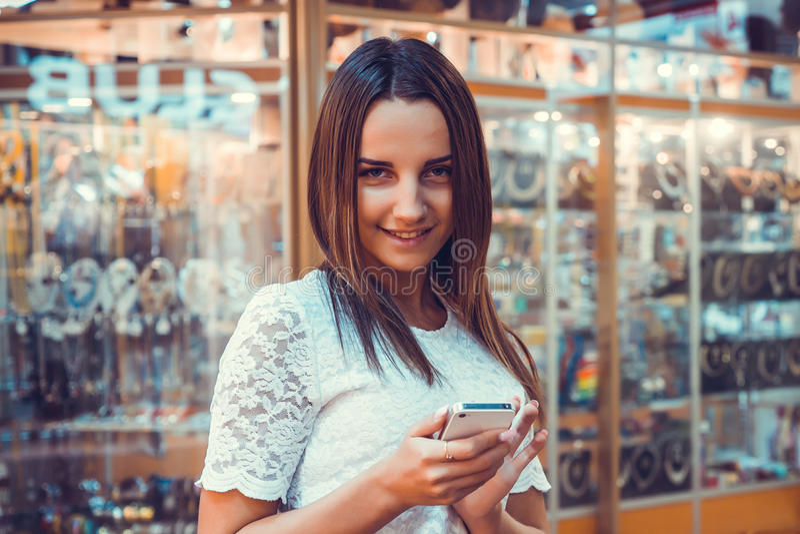Mädchen, das intelligentes Telefon lächelt und hält stockbilder