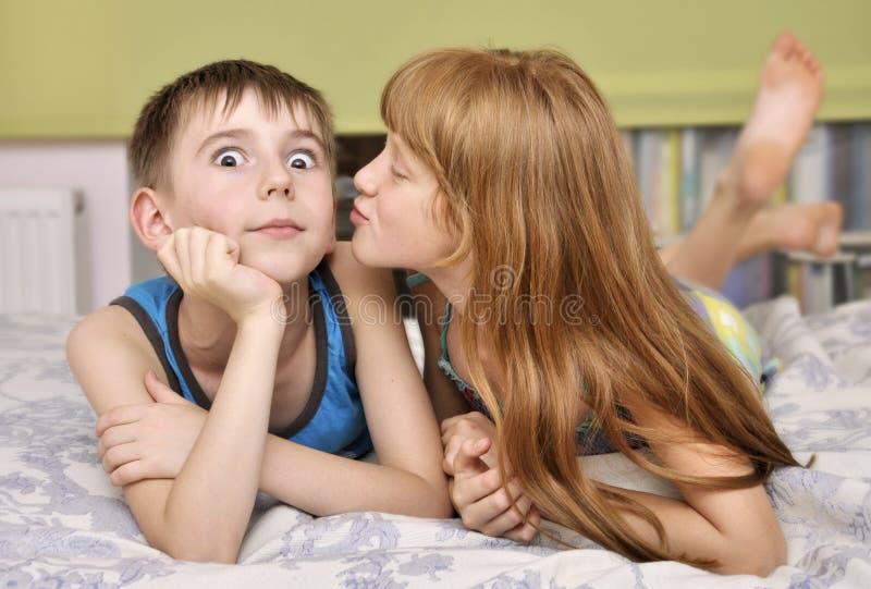 Mädchen, das Jungen auf Backe küßt stockbild