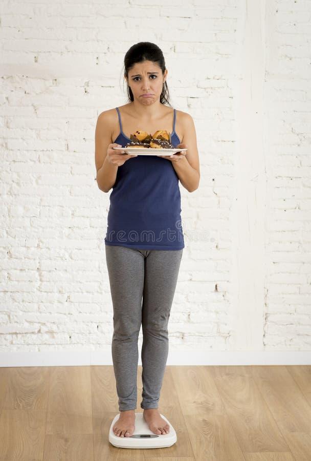 Mädchen, das Körpergewicht auf der Skala hält Behälter mit Zuckermuffin und Schokoladendonut überprüft stockfotografie