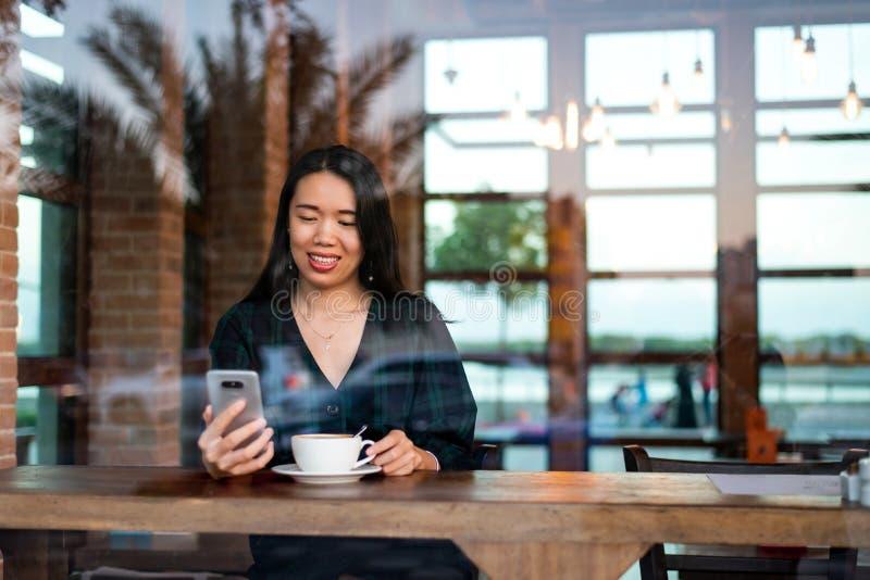 Mädchen, das Kaffee trinkt und Telefon in der Bar verwendet stockbild