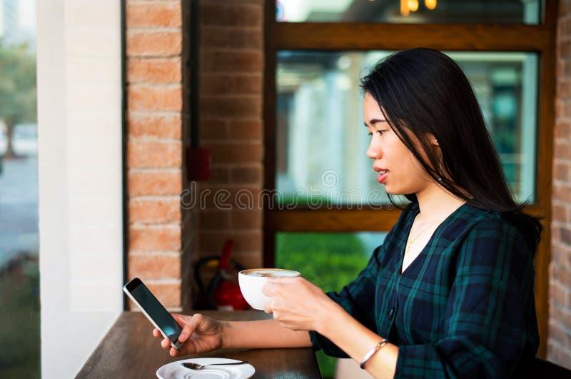 Mädchen, das Kaffee trinkt und Telefon in der Bar verwendet stockfotografie