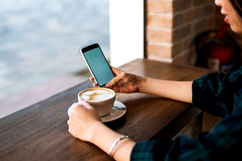 Mädchen, das Kaffee trinkt und Telefon in der Bar verwendet lizenzfreie stockfotografie