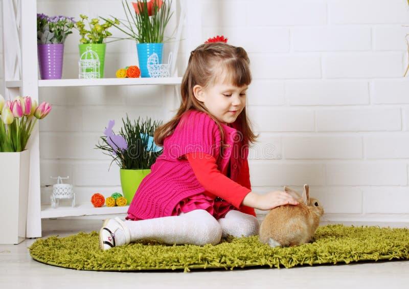 Mädchen, das Kaninchen streicht stockbild