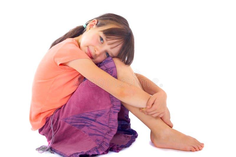 Mädchen, das Knie zum Kasten umarmt stockfoto