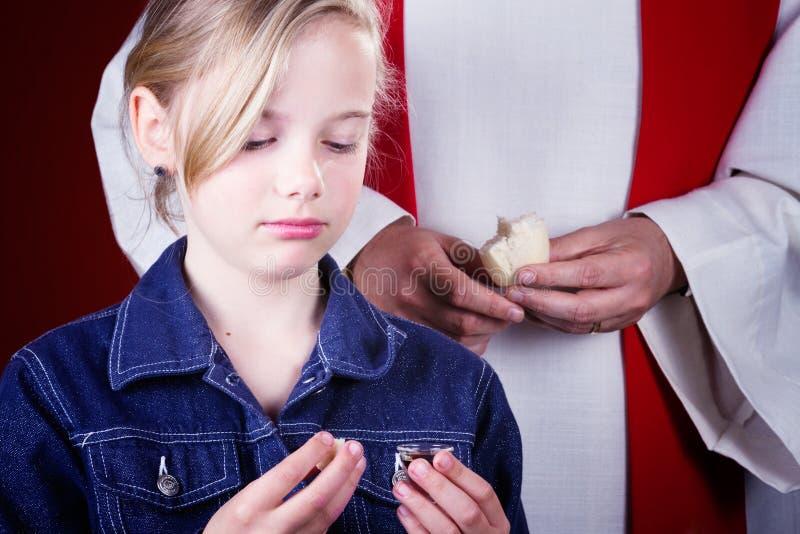 Mädchen, das Kommunion nimmt lizenzfreies stockfoto