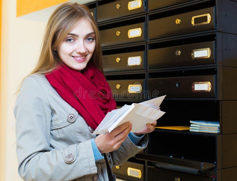 Mädchen, das Korrespondenz an der Lobby überprüft lizenzfreies stockfoto