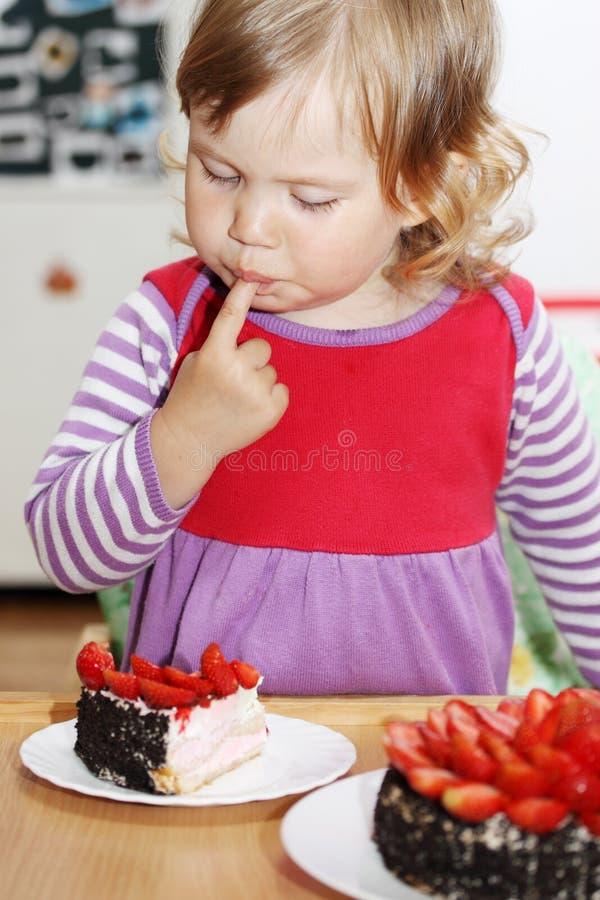 Mädchen, das Kuchen mit Erdbeeren isst stockbilder
