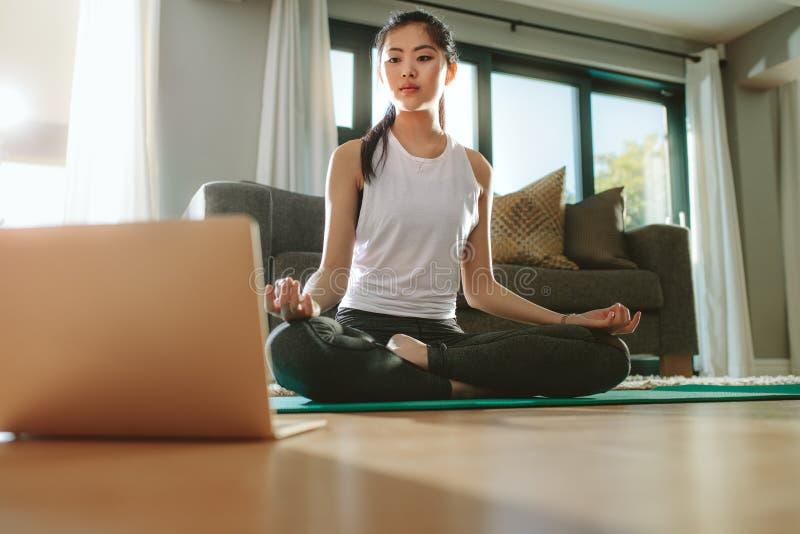 Mädchen, das Laptop betrachtet und zu Hause Yoga tut stockfotos