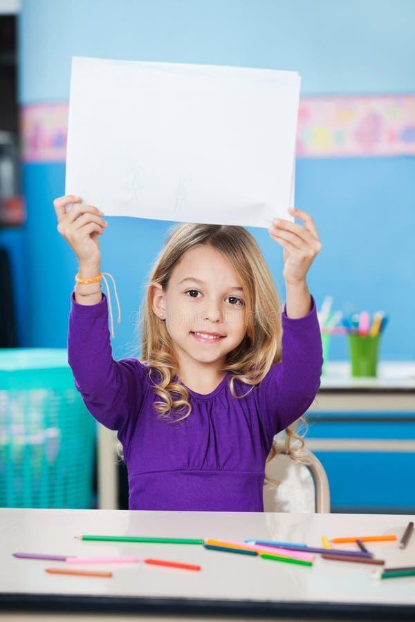 Mädchen, das leeres Papier am Schreibtisch im Klassenzimmer hält stockfotos