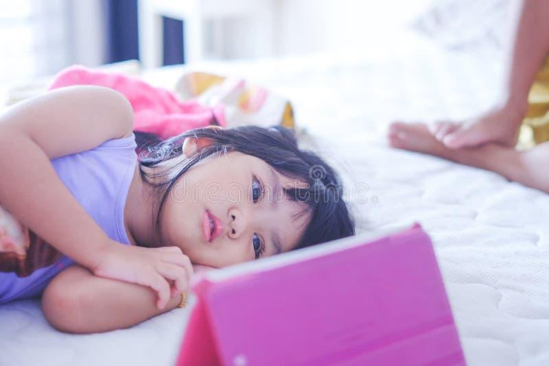 Mädchen, das on-line-Video auf Tablette aufpasst stockbilder