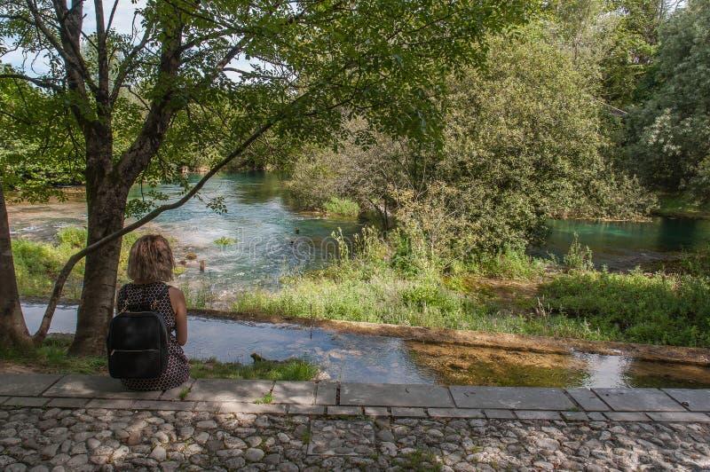 Mädchen, das Livenza-Flussquelle aufpasst stockfotos