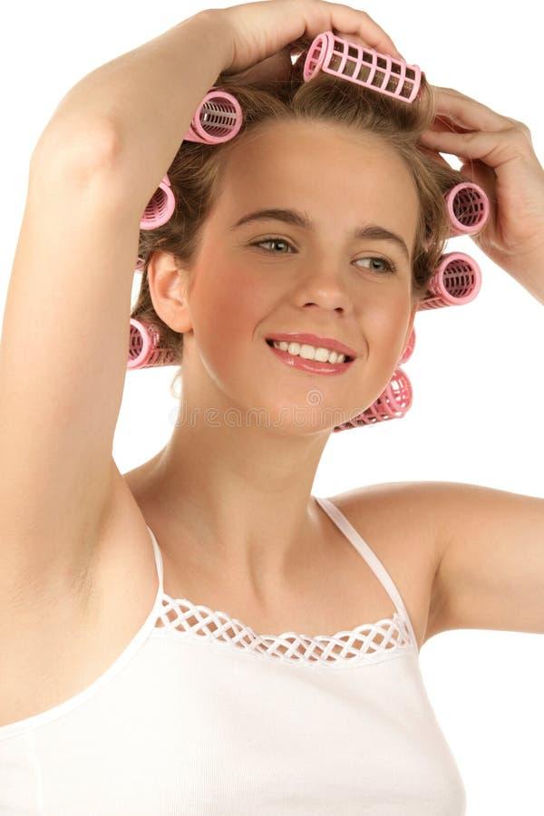 Mädchen, das Lockenwickler in Haar einsetzt stockfotografie
