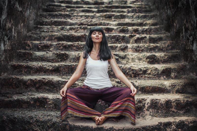 Mädchen, das in Lotussitz auf einem Steintreppenhaus sitzt lizenzfreie stockfotos