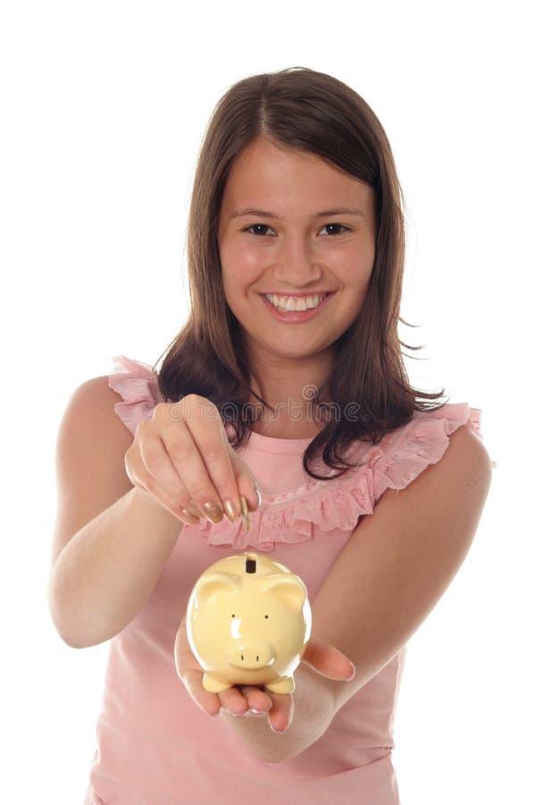Mädchen, das Münze in piggy Querneigung einsetzt lizenzfreie stockfotos