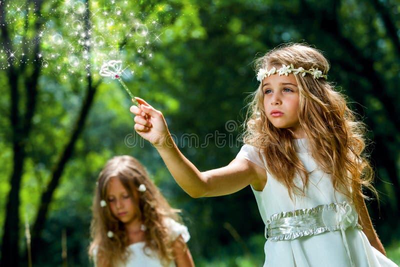 Mädchen, das magischen Stab im Holz wellenartig bewegt lizenzfreie stockfotos