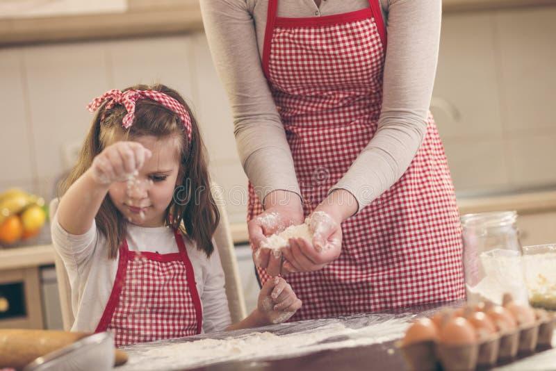 Mädchen, das Mehl auf der Küchenarbeitsplatte besprüht stockfotos