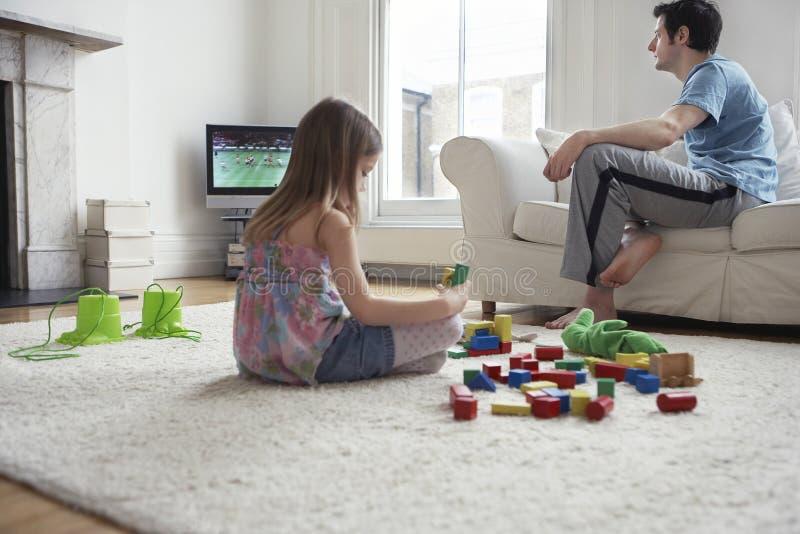 Mädchen, das mit Blöcken während Vater-Watching Fernsehen spielt stockbild