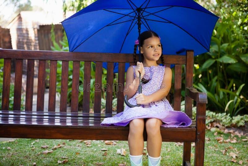 Mädchen, das mit blauem Regenschirm auf Holzbank sitzt lizenzfreie stockfotografie