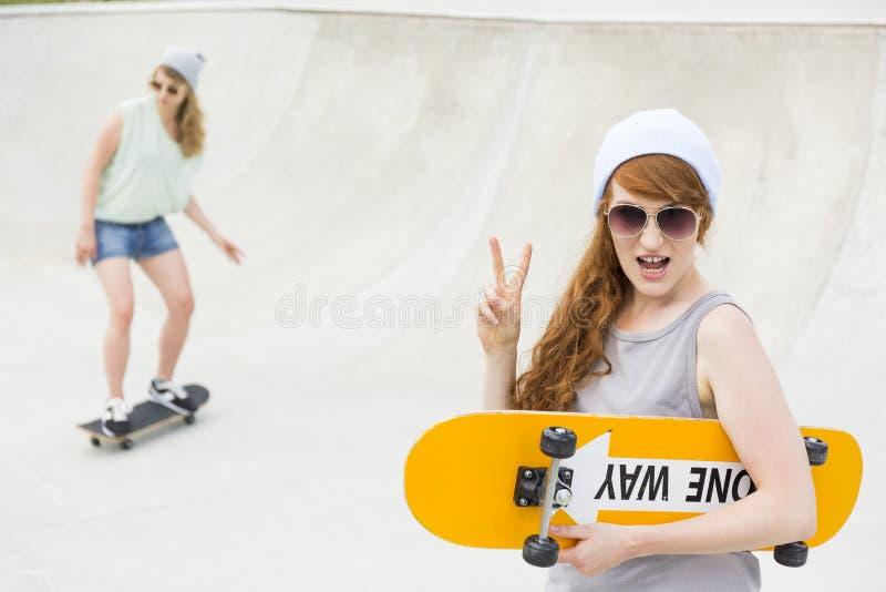Mädchen, das mit dem Skateboard steht lizenzfreies stockbild