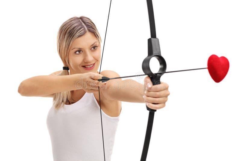 Mädchen, das mit einem Bogen und einem Liebespfeil zielt stockfoto