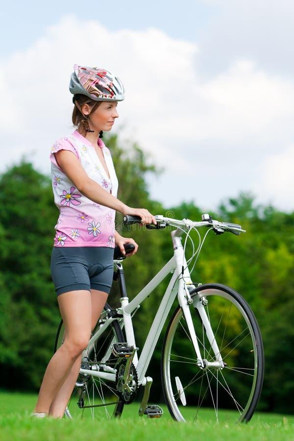 Mädchen, das mit einem Fahrrad steht lizenzfreies stockfoto
