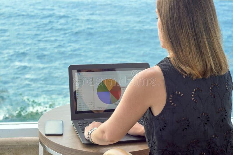 Mädchen, das mit einem Notizbuch auf der Terrasse eines Hotels betrachtet das Meer arbeitet stockfotos