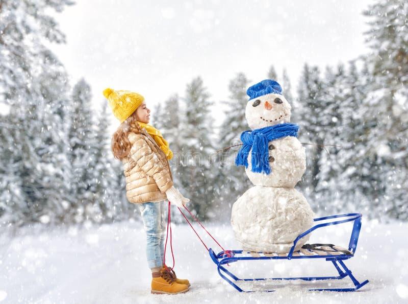 Mädchen, das mit einem Schneemann plaing ist lizenzfreie stockfotos