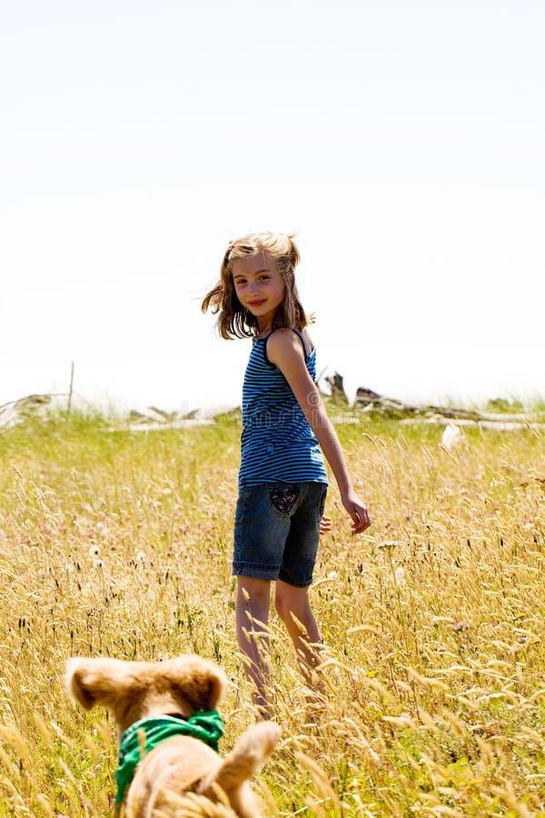Mädchen, das mit einem Welpen im hohen Gras spielt lizenzfreie stockbilder