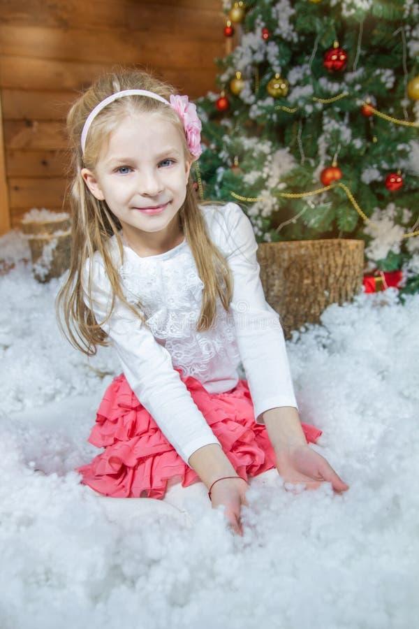 Mädchen, das mit Fauxschnee unter verziertem Weihnachtsbaum spielt lizenzfreie stockbilder