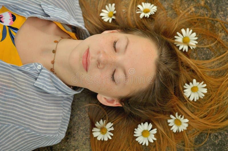 Mädchen, das mit Gänseblümchen auf ihrem Haar schläft lizenzfreies stockbild