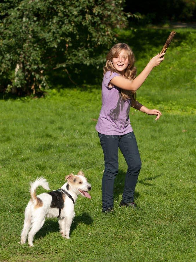 Mädchen, das mit Haustierhund spielt lizenzfreies stockbild