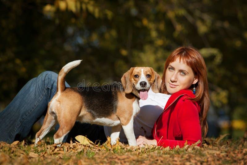 Mädchen, das mit ihrem Hund im Herbstpark spielt lizenzfreie stockbilder