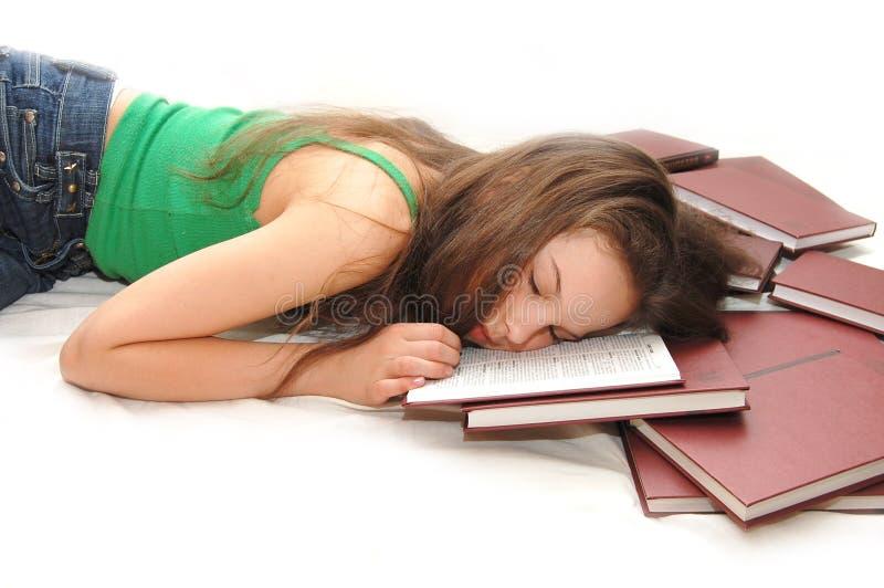 Mädchen, das mit ihrem Kopf auf einem geöffneten Buch schläft lizenzfreie stockbilder