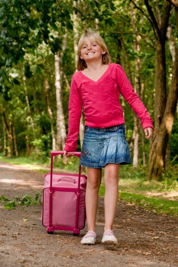 Mädchen, das mit ihrem rosafarbenen Koffer geht stockbilder