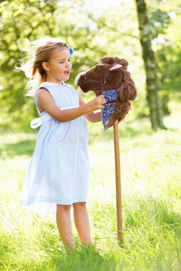 Mädchen, das mit Liebhaberei-Pferd auf dem Sommer-Gebiet spielt stockfoto