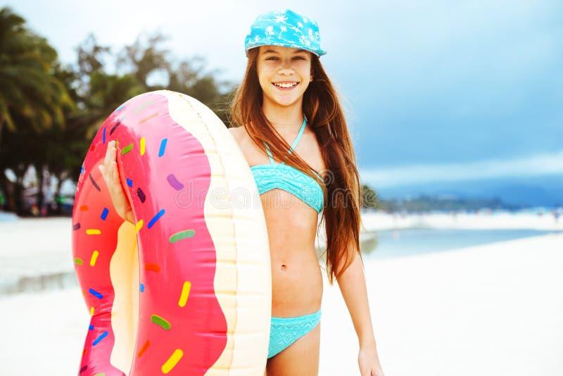 Mädchen, das mit lilo auf dem Strand sich entspannt lizenzfreies stockbild