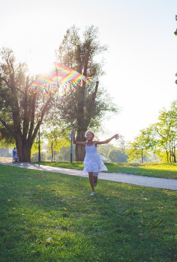 Mädchen, das mit Regenbogendrachen läuft Mischrasse - Afrikaner und Kaukasier Sommertag im Park lizenzfreie stockfotos