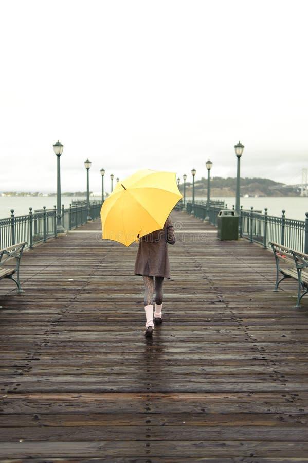 Mädchen, das mit Regenschirm geht stockbilder