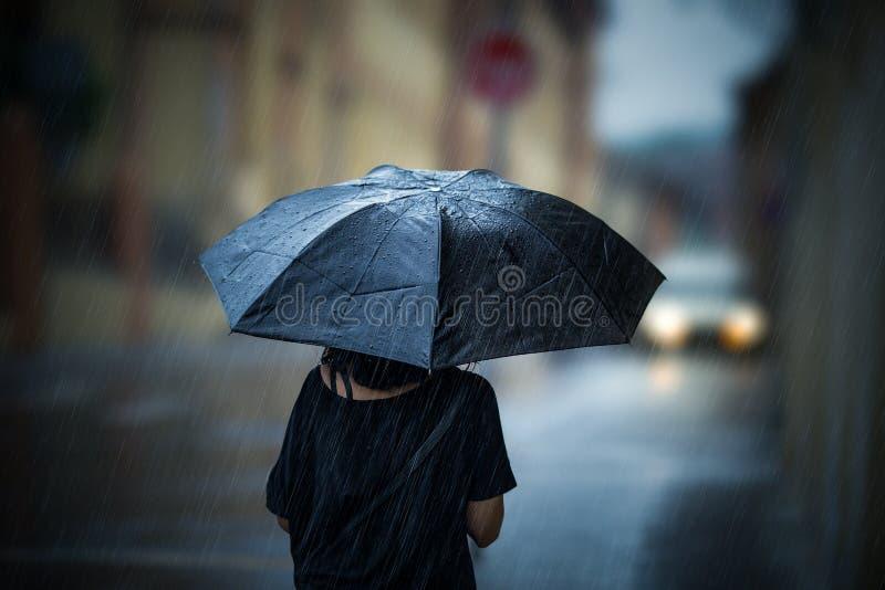 Mädchen, das mit Regenschirm geht lizenzfreies stockbild