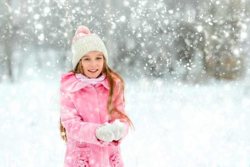 Mädchen, das mit Schnee an den Feiertagen spielt lizenzfreie stockbilder