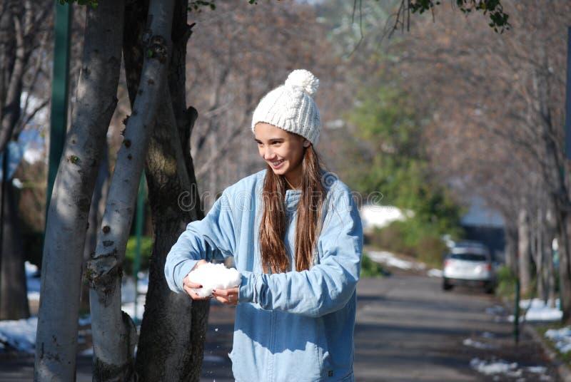 Mädchen, das mit Schnee spielt lizenzfreie stockfotografie