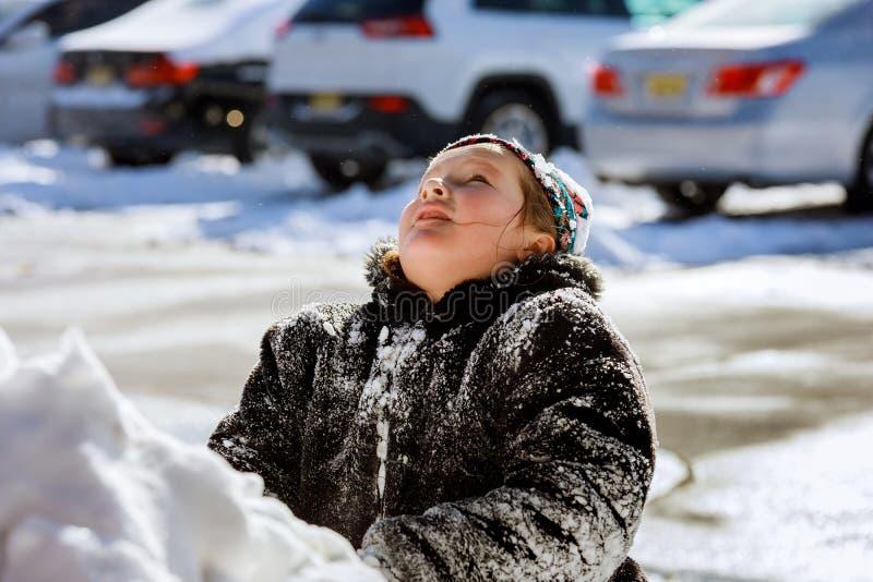 Mädchen, das mit Schnee spielt und oben schaut stockbild